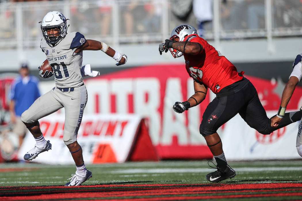 Utah State Aggies wide receiver Savon Scarver (81), left runs the ball against the UNLV Rebels during the first quarter of a football game at Sam Boyd Stadium in Las Vegas, Saturday, Oct. 21, 2017 ...