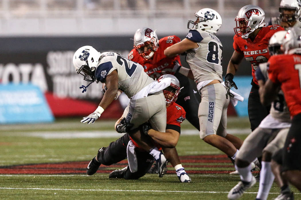 Utah State Aggies running back Tre Miller (20), left, is tackled by the UNLV Rebels during the fourth quarter of a football game at Sam Boyd Stadium in Las Vegas, Saturday, Oct. 21, 2017. Utah Sta ...