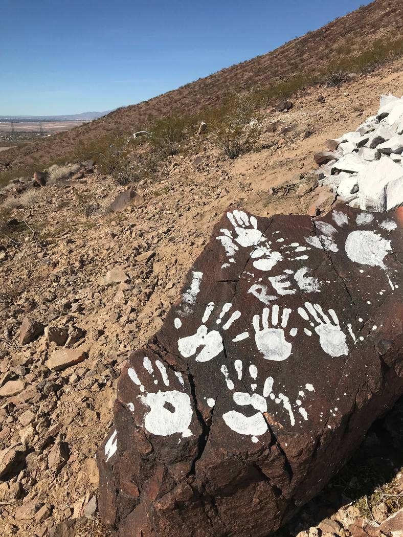 Messages and handprints are left on a rock just below a giant Q in honor of Quinton Robbins on Saturday, Oct. 21, 2017, on the mountain east of Basic High School in Henderson. Friends and family o ...