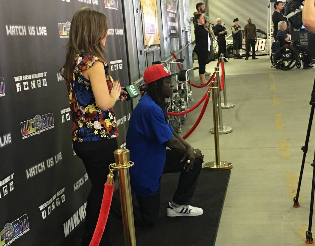 Flavor Flav breaks from an interview with KSNV-TV'S Jillian Lopez to take a knee during the national anthem during Mike Hammer's charity go-kart race at Gene Woods Racing on Sunday, Oct. 22, 2017. ...