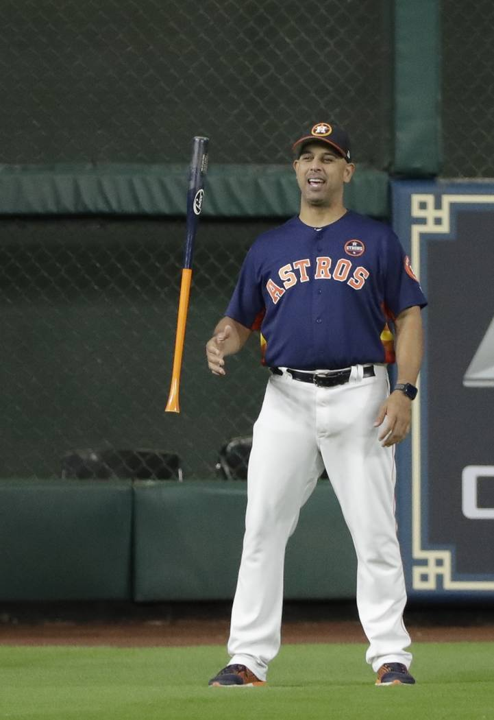 Houston Astros bench coach Alex Cora flips a bat before Game 6 of the American League Championship Series baseball game against the New York Yankees Friday, Oct. 20, 2017, in Houston. (AP Photo/Da ...