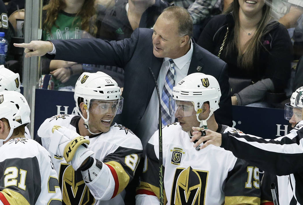 Vegas Golden Knights coach Gerard Gallant points from the bench, behind center Jonathan Marchessault (81) and right wing Reilly Smith (19) during the third period of an NHL hockey game against the ...