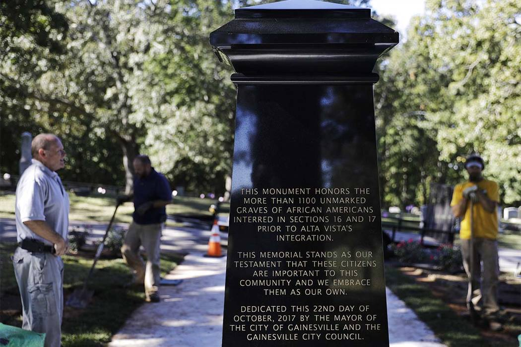 In this Friday, Oct. 20, 2017 photo, an inscription decorates a monument to honor African-Americans who were buried in unmarked graves in the previously segregated Alta Vista Cemetery in Gainesvil ...