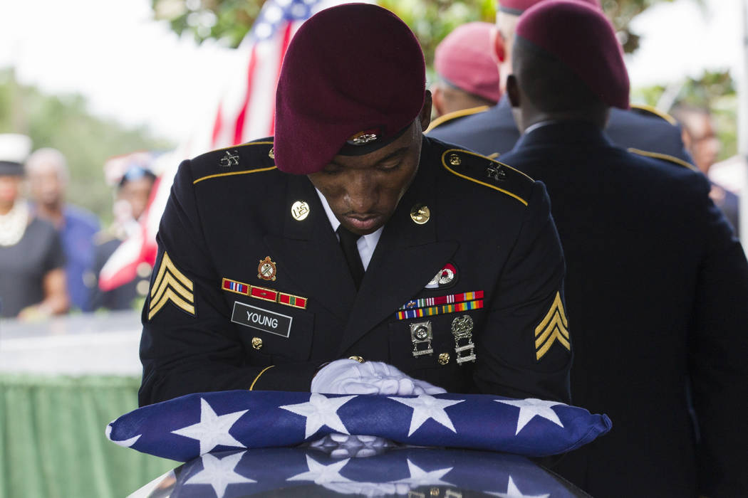 Sgt. Donald Young places a U.S. flag over the casket of Sgt. La David Johnson during his burial service at Fred Hunter's Hollywood Memorial Gardens in Hollywood, Fla., on Saturday, Oct. 21, 2017.  ...