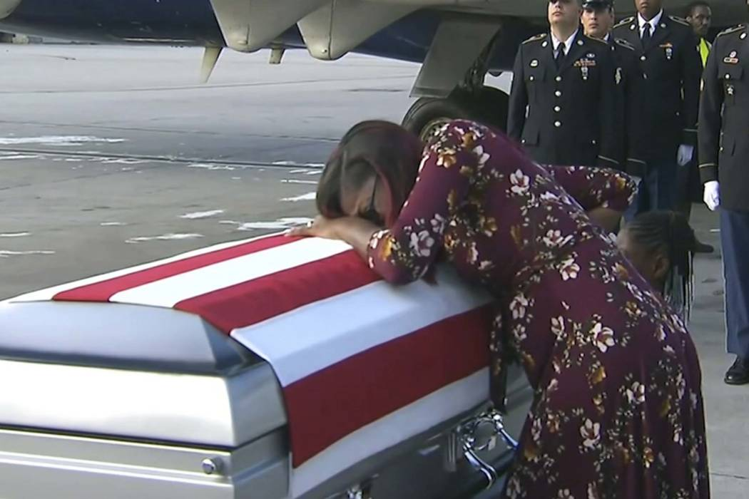 In this Tuesday, Oct. 17, 2017, frame from video, Myeshia Johnson cries over the casket in Miami of her husband, Sgt. La David Johnson, who was killed in an ambush in Niger. President Donald Trump ...