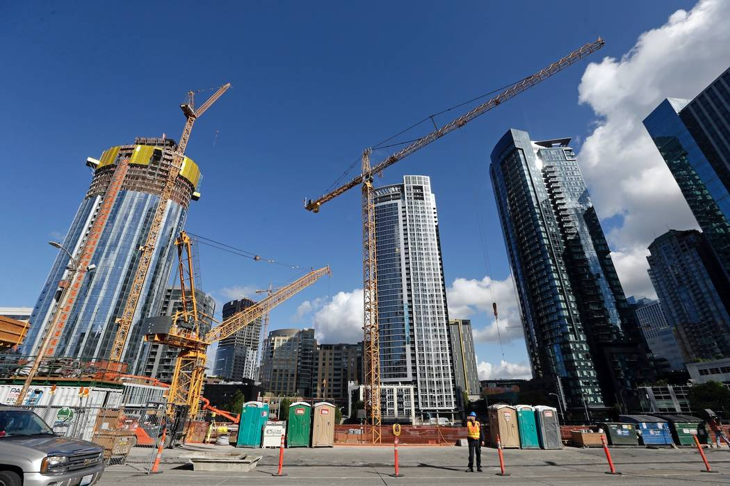 In this Wednesday, Oct. 11, 2017, photo, construction cranes fill a block across from an Amazon building in Seattle. Whichever city lands Amazon's second headquarters, some people in Seattle, it ...