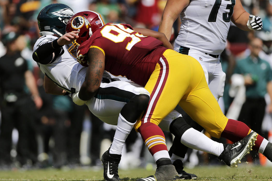 In this Sept. 10, 2017, file photo, Washington Redskins defensive end Jonathan Allen, right, knocks down Philadelphia Eagles quarterback Carson Wentz as Wentz throws a pass in the first half of an ...