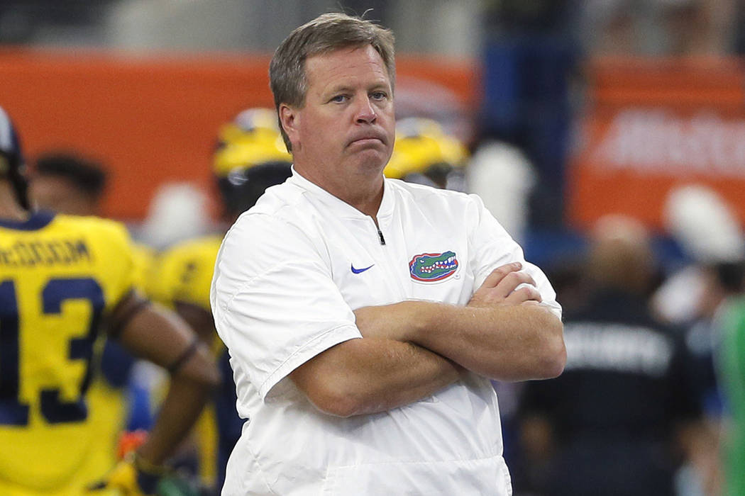 This is a Sept. 2, 2017, file photo showing Florida head coach Jim McElwain watching his team warm up before an NCAA college football game against Michigan, in Arlington, Texas. (AP Photo/Tony Gut ...