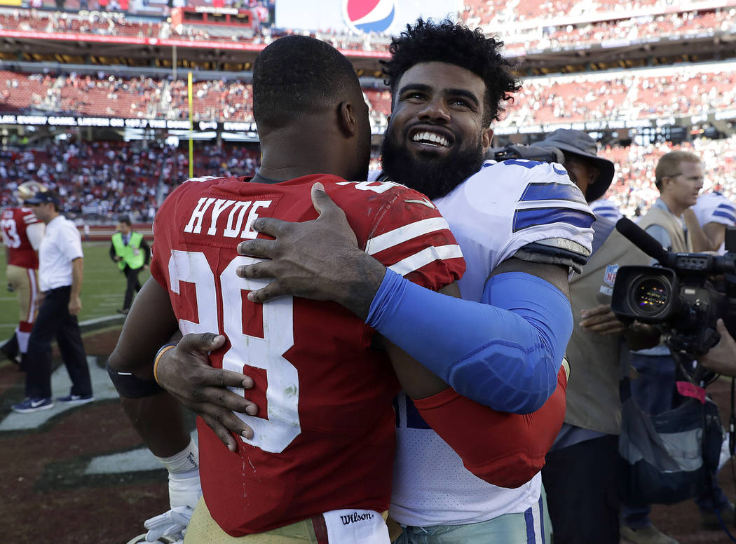 San Francisco 49ers running back Carlos Hyde (28) hugs Dallas Cowboys running back Ezekiel Elliott after the Cowboys beat the 49ers in an NFL football game in Santa Clara, Calif., Sunday, Oct. 22, ...