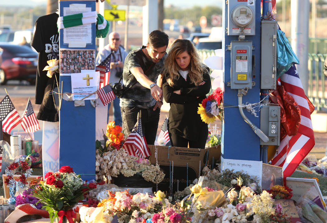 Francesco Floris, left, and Irene Corzo, both of Italy, visit a memorial at the Welcome to Fabulous Las Vegas sign in Las Vegas, Tuesday, Oct. 17, 2017, honoring the victims of the Route 91 Harves ...