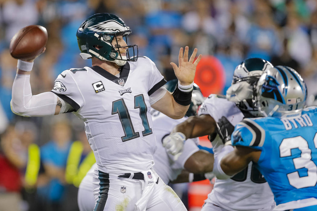 FILE - In this Thursday, Oct. 12, 2017 file photo, Philadelphia Eagles' Carson Wentz (11) aims a pass against the Carolina Panthers during the second half of an NFL football game in Charlotte, N.C ...
