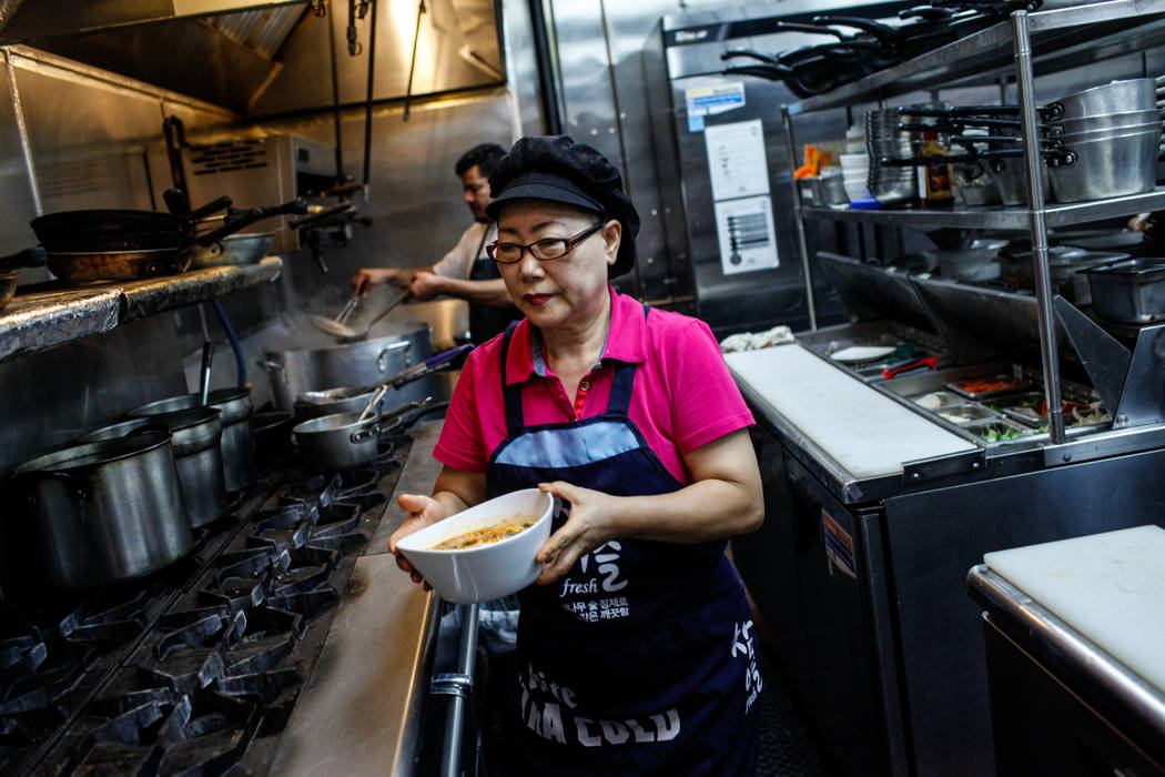 Myung Ja Kim, 59, of Las Vegas, carries a bowl of noodles to be served at Lee's Korean BBQ in Las Vegas, Tuesday, Oct. 24, 2017. Owner Hae Un Lee attended a meeting Tuesday addressing Asian restau ...