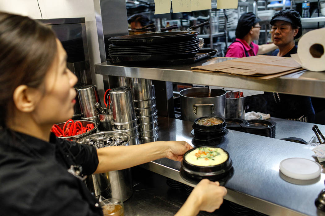Grace Kim, 48, of Las Vegas, left, grabs food prepared in the kitchen before serving it to customers at Lee's Korean BBQ in Las Vegas, Tuesday, Oct. 24, 2017. Owner Hae Un Lee attended a meeting T ...