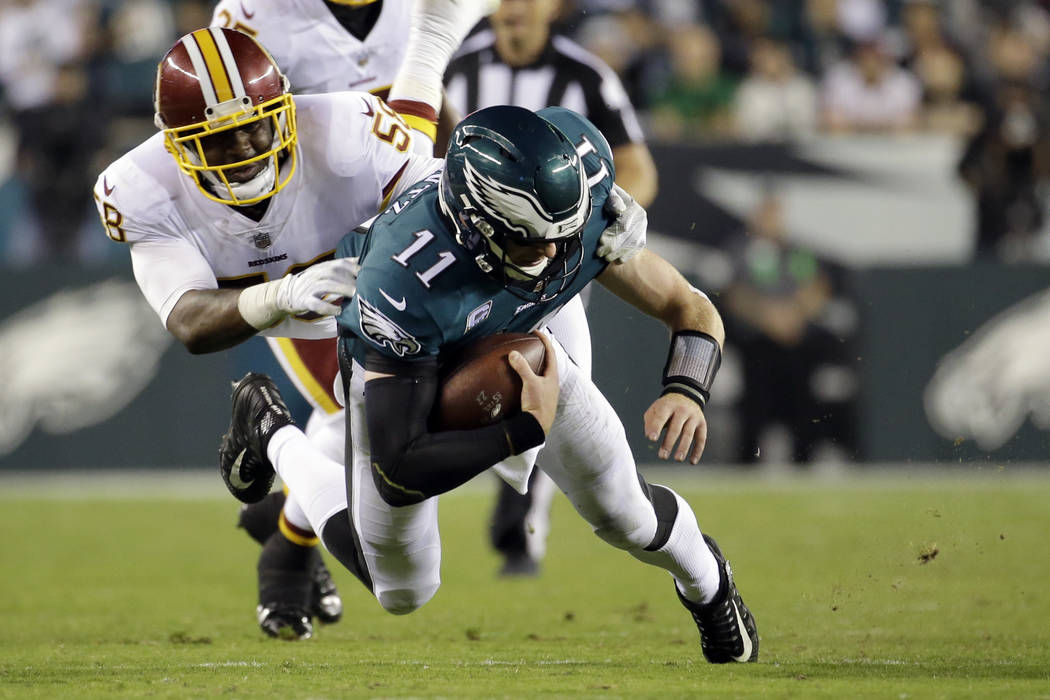 Philadelphia Eagles quarterback Carson Wentz (11) dives forward as Washington Redskins linebacker Junior Galette (58) tries to stop him during the second half of an NFL football game, Monday, Oct. ...