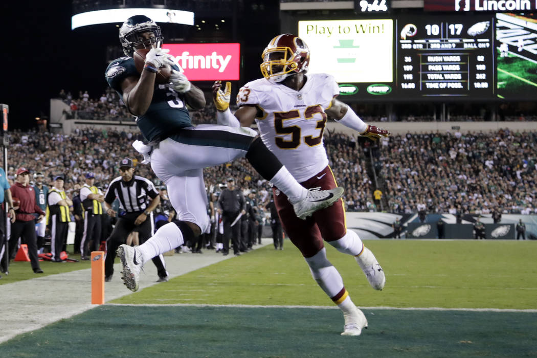 Philadelphia Eagles running back Corey Clement, left, makes a touchdown catch on a pass from quarterback Carson Wentz, not pictured, as Washington Redskins inside linebacker Zach Brown (53) defend ...