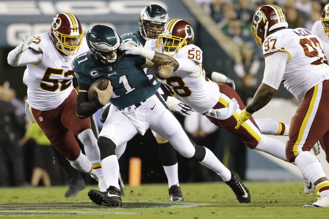 Washington Redskins linebacker Junior Galette (58) grabs at the facemask of Philadelphia Eagles quarterback Carson Wentz (11) during the first half of an NFL football game, Monday, Oct. 23, 2017,  ...