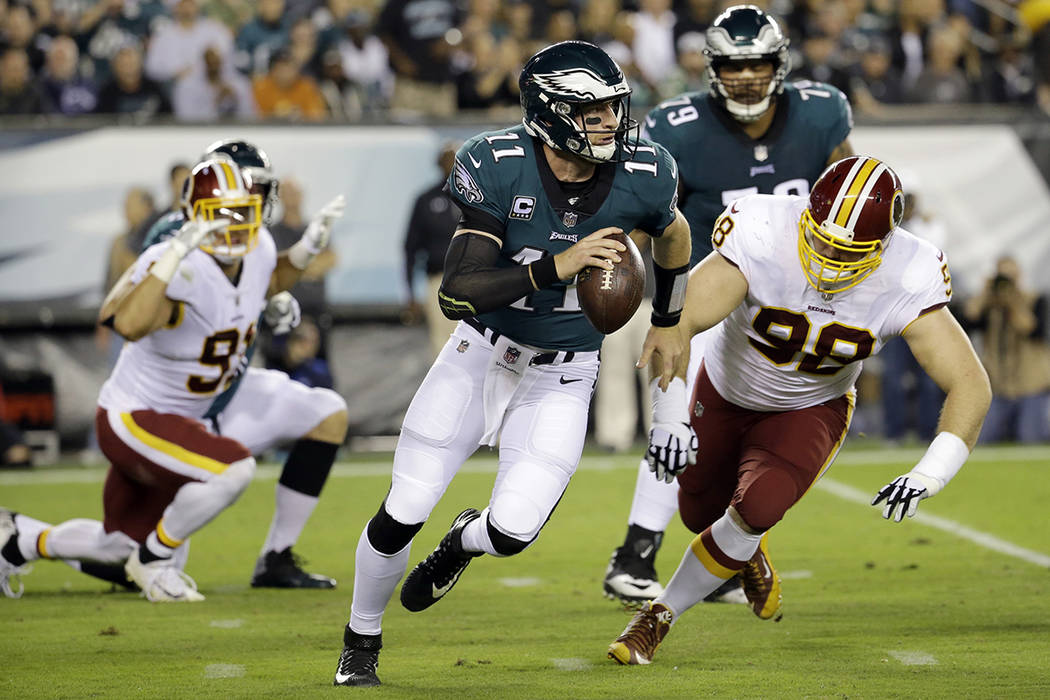 Philadelphia Eagles quarterback Carson Wentz (11) scrambles as Washington Redskins defensive tackle Matthew Ioannidis (98) chases him during the first half of an NFL football game, Monday, Oct. 23 ...
