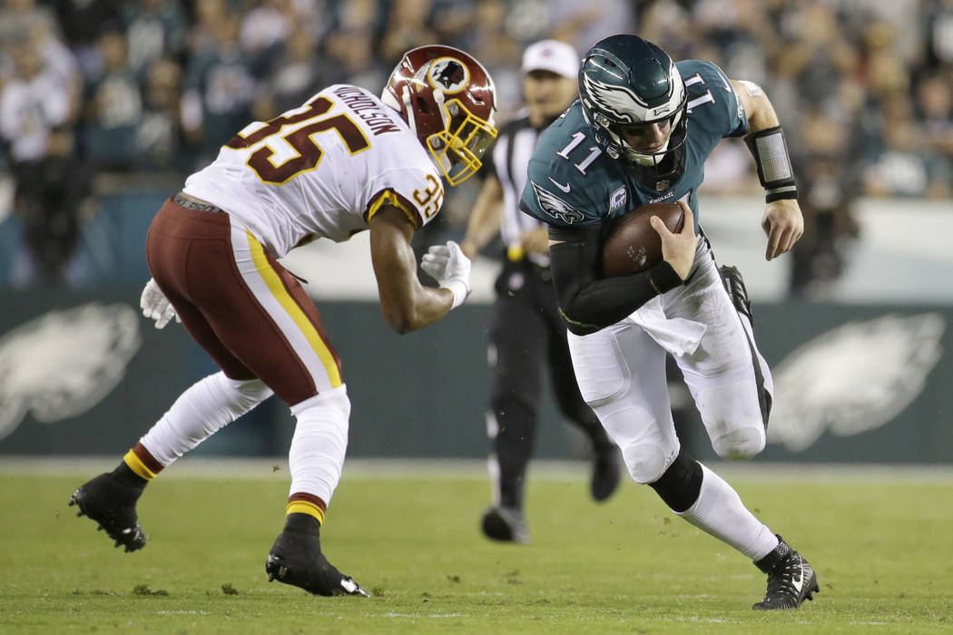 Philadelphia Eagles quarterback Carson Wentz (11) runs for yardage as Washington Redskins strong safety Montae Nicholson (35) tries to make a hit during the second half of an NFL football game, Mo ...