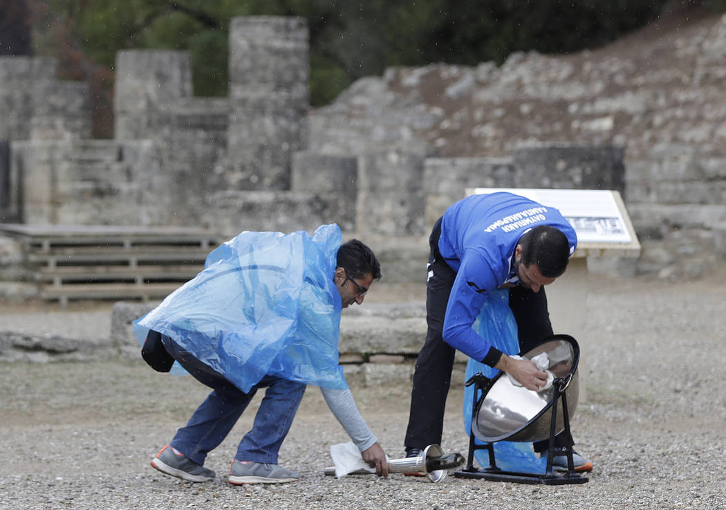 Officials try to dry rain from the cauldron before the lighting ceremony of the Olympic flame in Ancient Olympia, southwestern Greece, on Tuesday, Oct. 24, 2017. The flame will be transported by t ...