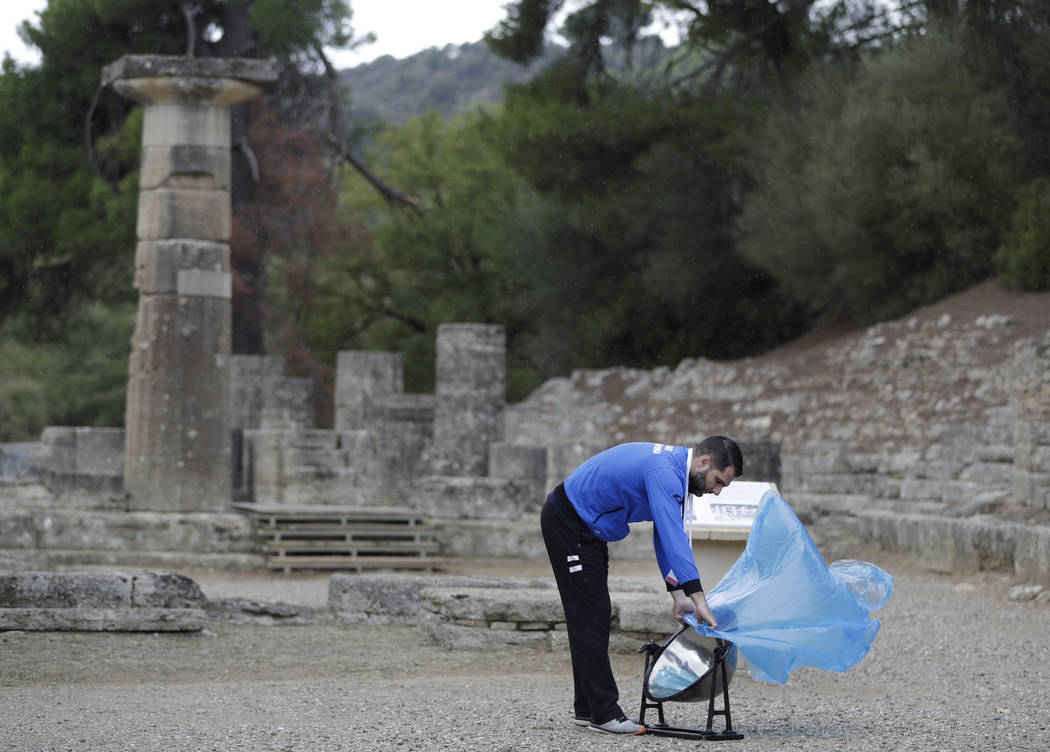 An official places a cover over the cauldron to protect it from rain before the lighting ceremony of the Olympic flame in Ancient Olympia, southwestern Greece, on Tuesday, Oct. 24, 2017. The flame ...