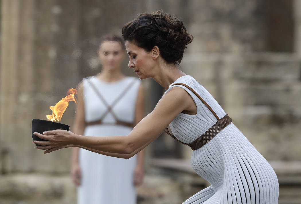 Actress Katerina Lehou as high priestess, carries a bowl of fire during the lighting ceremony of the Olympic flame in Ancient Olympia, southwestern Greece, on Tuesday, Oct. 24, 2017. The flame wil ...