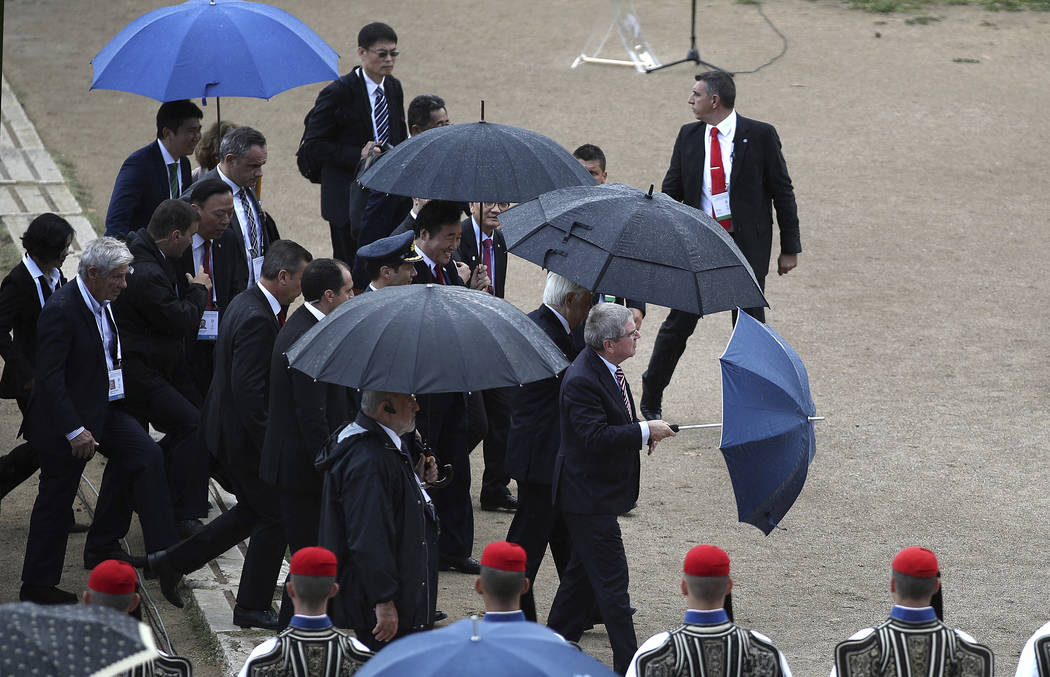 Dignitaries, including IOC President Thomas Bach, bottom right, and South Korea's Prime Minister Lee Nak-yon, center, shelter fro the rain during the lighting ceremony of the Olympic flame in Anci ...