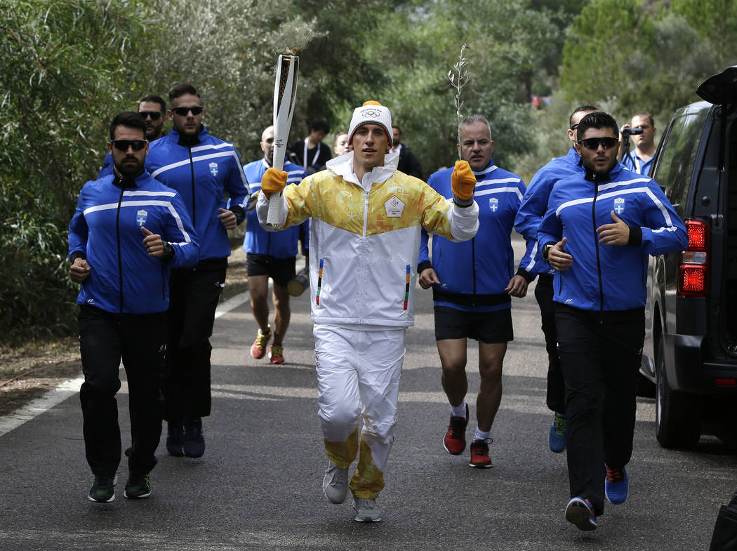 Torch bearer Greek cross-country skier Apostolos Angelis runs with the Olympic flame during the lighting ceremony of the Olympic flame in Ancient Olympia, southwestern Greece, on Tuesday, Oct. 24, ...