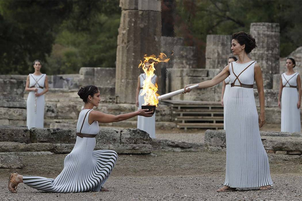 Actress Katerina Lehou, right, as high priestess, lights the torch during the lighting ceremony of the Olympic flame in Ancient Olympia, southwestern Greece, on Tuesday, Oct. 24, 2017. The flame w ...