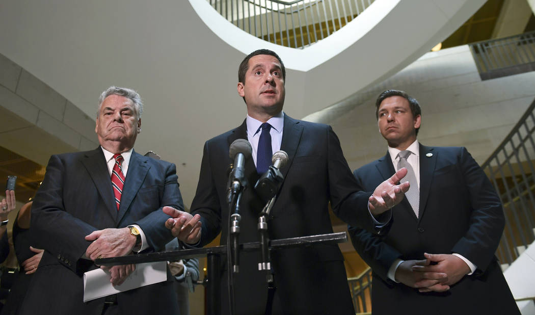 House Intelligence Committee Chairman Rep. Devin Nunes, R-Calif., center, standing with Rep. Peter King, R-N.Y., left, and Rep. Ron DeSantis, R-Fla., right, speaks on Capitol Hill in Washington, T ...