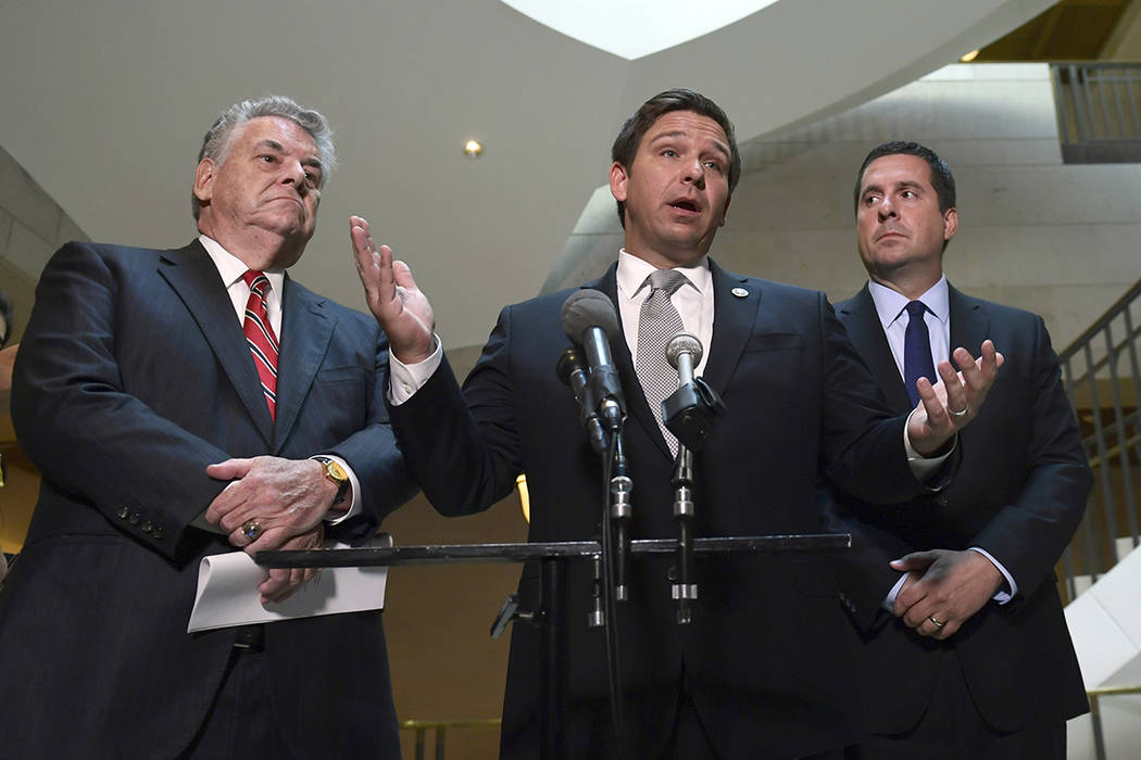 Rep. Ron DeSantis, R-Fla., center, standing with Rep. Peter King, R-N.Y., left, and House Intelligence Committee Chairman Rep. Devin Nunes, R-Calif., right, speaks on Capitol Hill in Washington, T ...