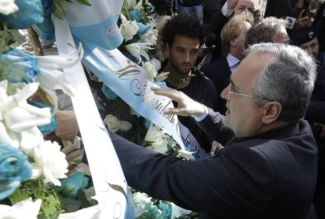 Lazio soccer team president Claudio Lotito, accompanied by Lazio player Felipe Anderson, center, places a wreath outside Rome's Synagogue, Tuesday, Oct. 24, 2017. Lazio fans have a long history of ...