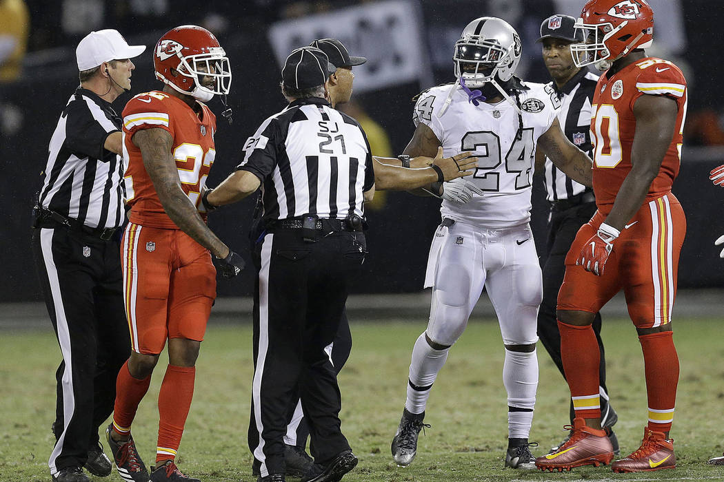 Oakland Raiders running back Marshawn Lynch (24) talks with officials before he was ejected during the first half of an NFL football game between the Raiders and the Kansas City Chiefs in Oakland, ...