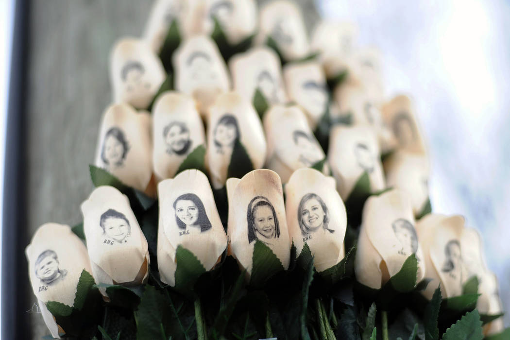 White roses with the faces of victims of the Sandy Hook Elementary School shooting are attached to a telephone pole near the school in Newtown, Conn. on  Jan. 14, 2013. (Jessica Hill/AP)