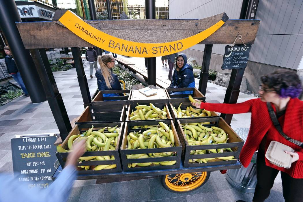 In this Wednesday, Oct. 11, 2017, photo, people grab bananas from a free banana stand provided by Amazon in Seattle. Memo to the many places vying for Amazon's second headquarters: It ain't all fo ...