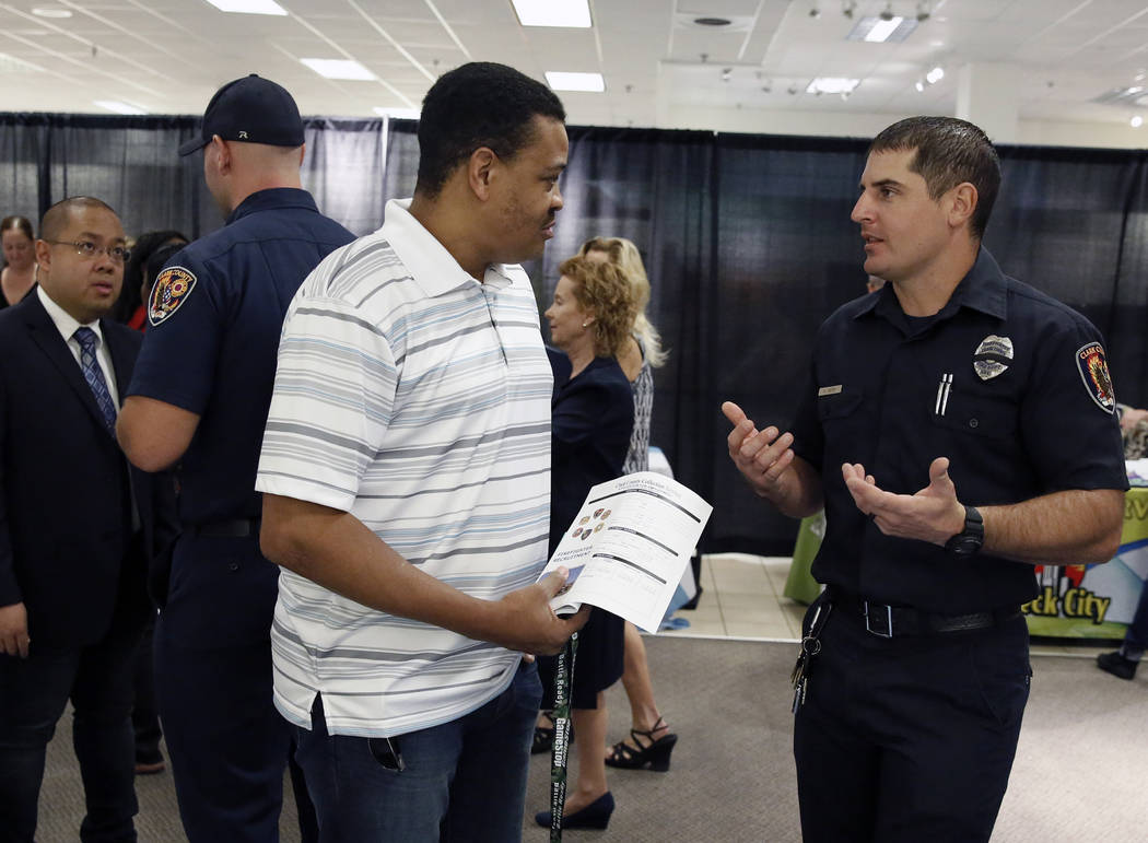 Clark County firefighter, Adam Smith, right, talks to Anthony Lyons of Henderson during the Nevada Day Super Hiring Event on Wednesday, Oct. 25, 2017 at the Boulevard Mall in Las Vegas. Bizuayehu  ...