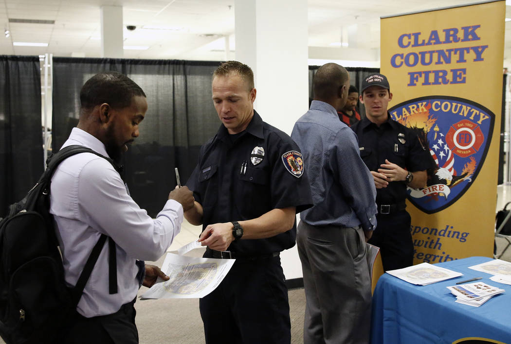 Clark County firefighter, James King, second right, talks to Sherrod Lewis during the Nevada Day Super Hiring Event on Wednesday, Oct. 25, 2017 at the Boulevard Mall in Las Vegas. Bizuayehu Tesfay ...