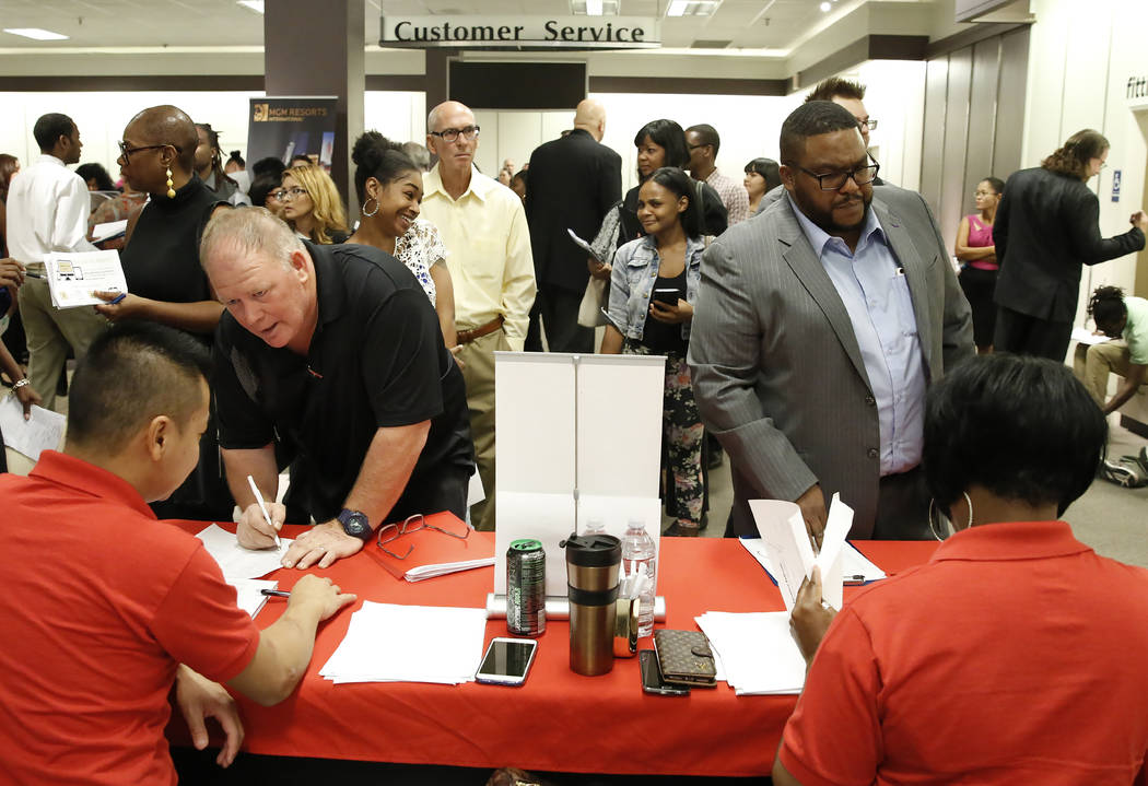 Job seekers, including Andre Peterson, right, speak to recruiters with Station Casino during the Nevada Day Super Hiring Event on Wednesday, Oct. 25, 2017 at the Boulevard Mall in Las Vegas. Bizua ...