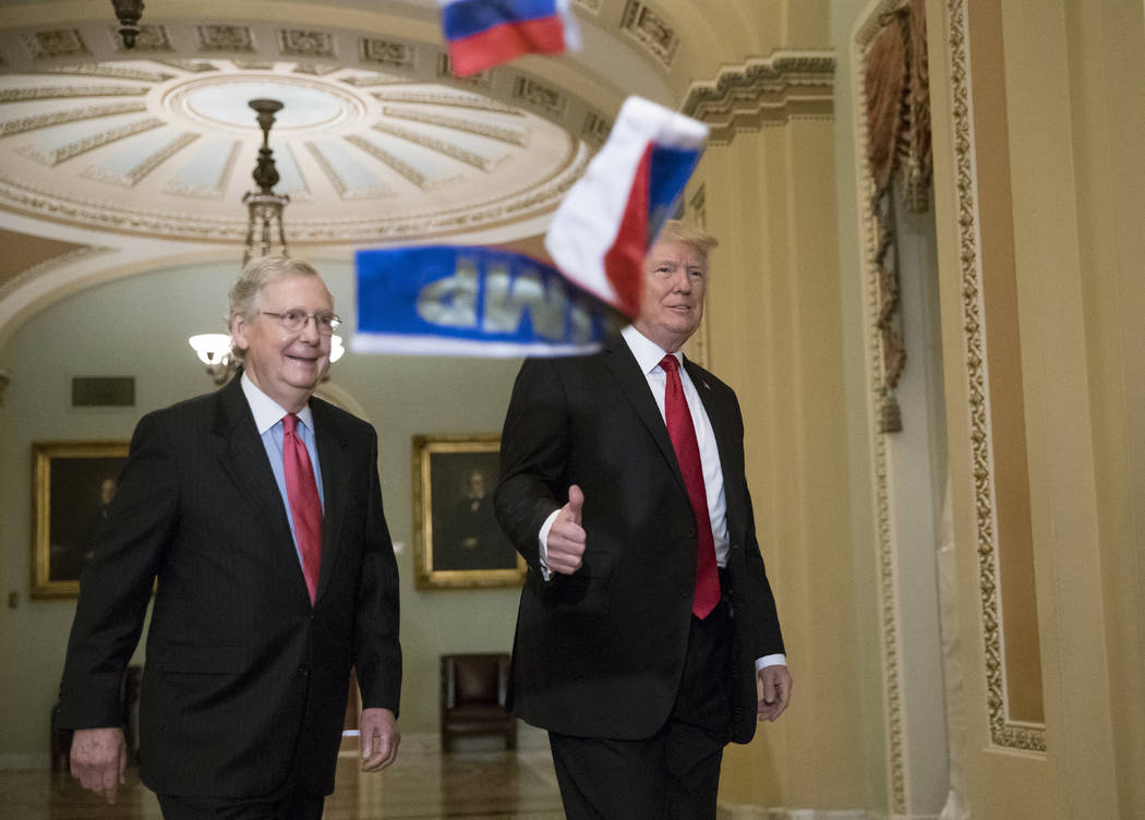 "Small Russian flags bearing the word ""Trump"" are thrown by a protester toward President Donald Trump, as he walks with Senate Majority Leader Mitch McConnell, R-Ky., on Capitol Hill to have lunch  ..."