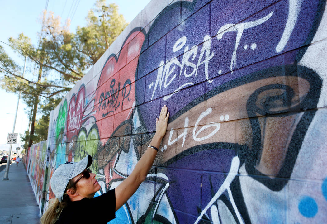 Mynda Smith touches her sister's, Neysa Tonks, name painted on a mural off of Westcliff Drive and Antelope Way in Las Vegas, Tuesday, Oct. 24, 2017. The mural was painted in one night with the nam ...