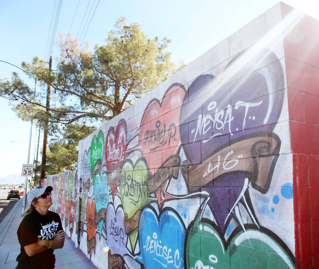 Mynda Smith looks at her sister's, Neysa Tonks, name painted on a mural off of Westcliff Drive and Antelope Way in Las Vegas, Tuesday, Oct. 24, 2017. The mural was painted in one night with the na ...