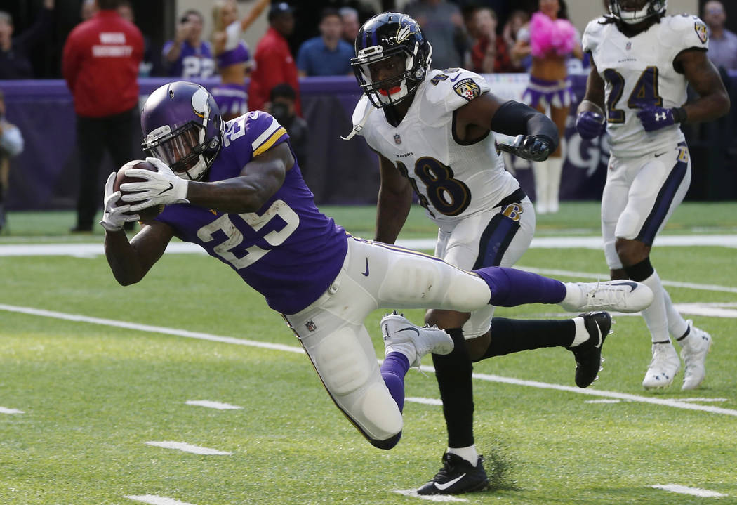Minnesota Vikings running back Latavius Murray (25) dives to the end zone ahead of Baltimore Ravens outside linebacker Patrick Onwuasor (48) during a 29-yard touchdown run in the second half of an ...