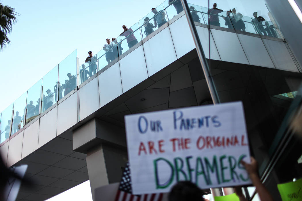 Tourists watch as several hundred Deferred Action for Childhood Arrival program (DACA) recipients and supporters march down the Strip in Las Vegas, Sunday, Sept. 10, 2017, to call on President Don ...