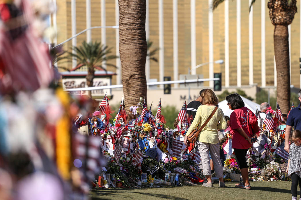 People visit a memorial at the Welcome to Fabulous Las Vegas sign in Las Vegas, Monday, Oct. 16, 2017, honoring the victims of the Route 91 Harvest Festival mass shooting. Joel Angel Juarez Las Ve ...