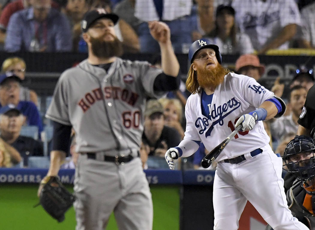 Los Angeles Dodgers' Justin Turner watches his two-run home run off Houston Astros starting pitcher Dallas Keuchel during the sixth inning of Game 1 of baseball's World Series Tuesday, Oct. 24, 20 ...