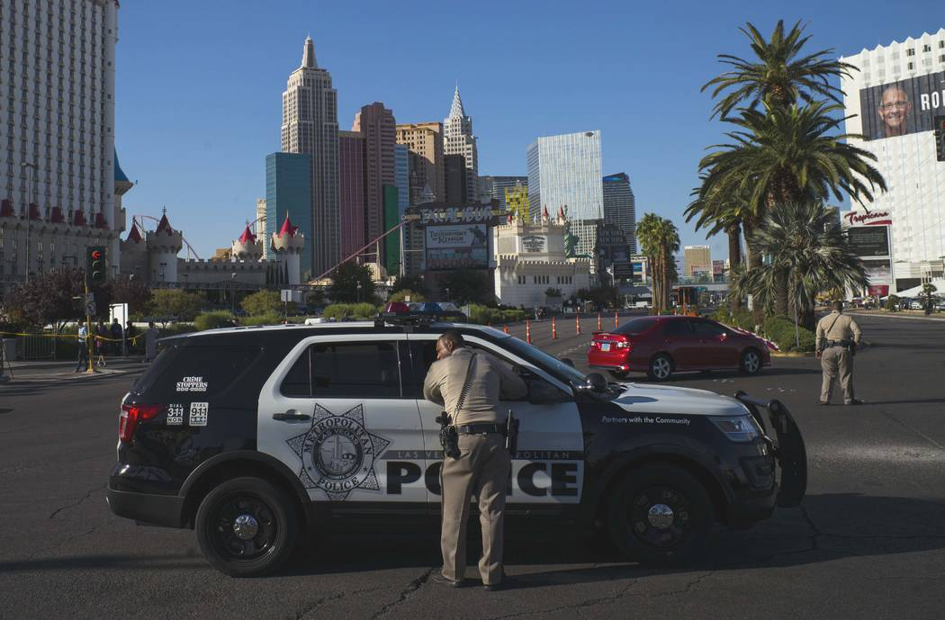 Las Vegas police officers talk at Las Vegas Boulevard and Reno Avenue outside of the Luxor, near the Route 91 Harvest festival grounds in Las Vegas on Tuesday, Oct. 3, 2017. A gunman opened fire o ...