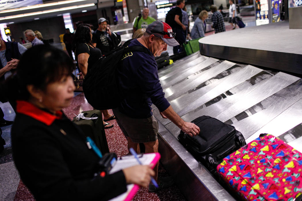 A man picks up his luggage at McCarran International Airport Terminal 1 baggage claim in Las Vegas, Friday, Oct. 13, 2017. (Joel Angel Juarez Las Vegas Review-Journal)