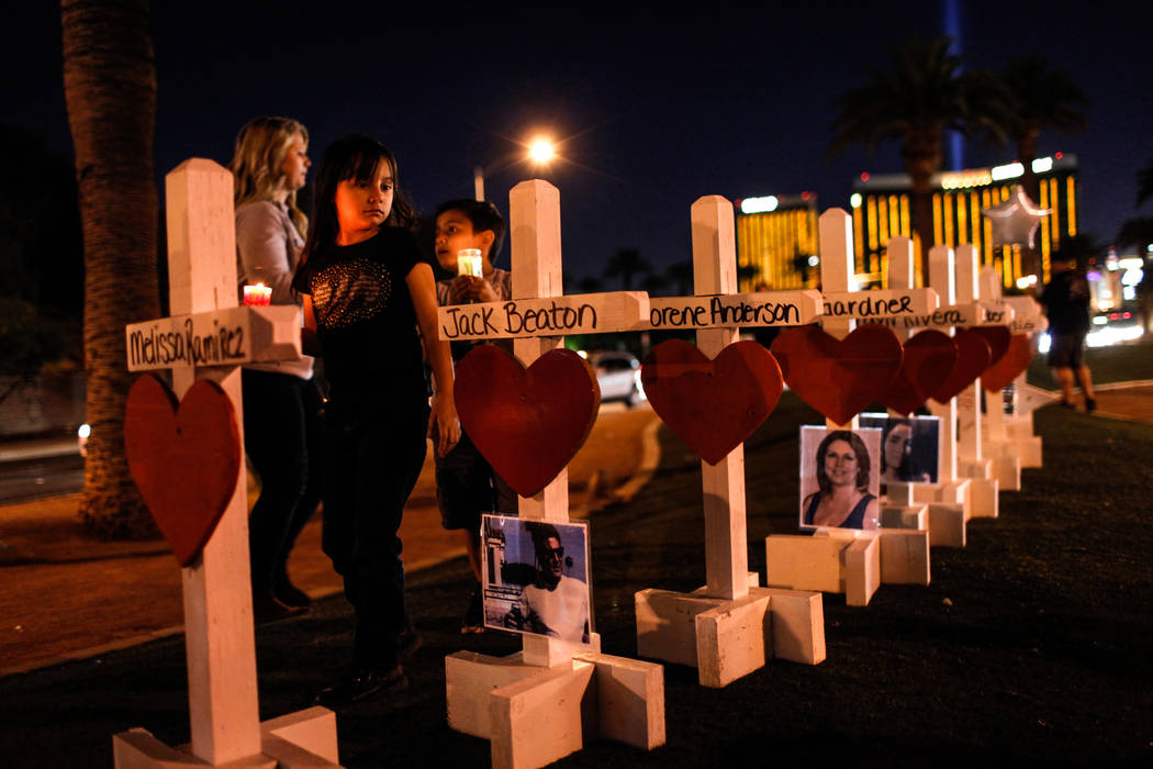 Jessica Reyes of Las Vegas, 7, holds a candle as she walks past crosses honoring the victims of Sunday night's shooting during a vigil at the Welcome to Fabulous Las Vegas sign in Las Vegas, Thurs ...