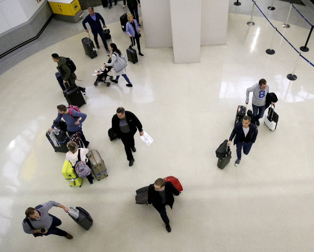 Passengers walk with their luggage as they exit customs and immigration at the international arrivals terminal at Newark Liberty International Airport, Thursday, Oct. 26, 2017, in Newark, N.J. . L ...