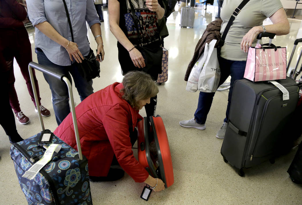 Donna Basquille, of Luton, England, zips up her luggage while talking to acquaintances after meeting them off her flight from London at the international arrival terminal at Newark Liberty Interna ...