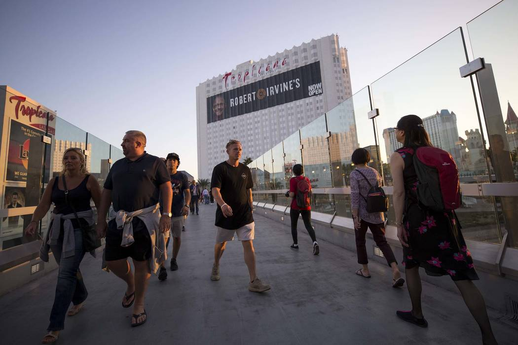 People walk over a pedestrian bridge linking the MGM Grand and the Tropicana near the intersection of Las Vegas Boulevard and Tropicana Avenue in Las Vegas, Thursday, Oct. 12, 2017. (Richard Brian ...